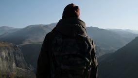 Homem do caminhante que olha as montanhas e a skyline filme