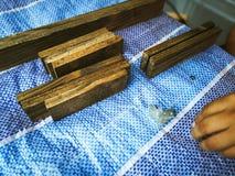 Homem do carpinteiro para arranjar a prancha de madeira imagem de stock