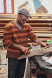 Homem do carpinteiro que trabalha na oficina imagem de stock