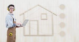 Homem do carpinteiro do trabalhador manual do conceito da renovação da construção da casa com ícones vazios dos símbolos do lapto imagem de stock