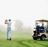 Homem do carrinho de golfe fotografia de stock