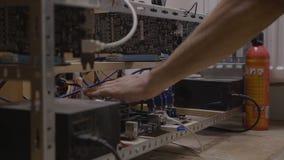 Homem do coordenador do técnico que verifica conexões e temperatura de cabo no equipamento cripto da mineração da moeda - filme