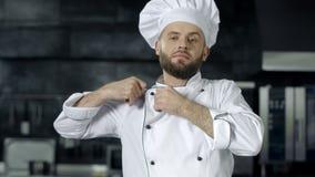 Homem do cozinheiro chefe que prepara-se para cozinhar na cozinha do restaurante Retrato do cozinheiro masculino sério filme