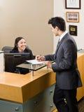 Homem do cumprimento do recepcionista na mesa dianteira Fotos de Stock