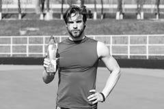 Homem do desportista que guarda a garrafa plástica da água potável imagens de stock