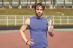 Homem do desportista que guarda a garrafa plástica da água potável fotografia de stock royalty free