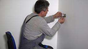 Homem do eletricista com chave de fenda para conectar o soquete elétrico aos fios vídeos de arquivo