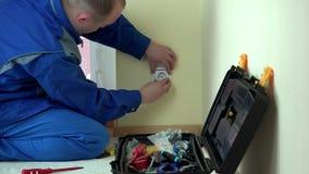 Homem do eletricista com tensão do teste do verificador da chave de fenda no soquete da tomada elétrica vídeos de arquivo