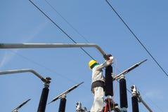 Homem do eletricista que trabalha no polo de alta tensão Fotografia de Stock Royalty Free