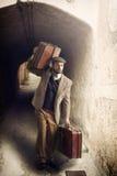 Homem do emigrante com as malas de viagem em uma cidade pequena Fotografia de Stock