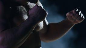 Homem do encaixotamento pronto para lutar Pugilista com mãos fortes e os punhos apertados em um fundo preto Close-up da mão do pu foto de stock