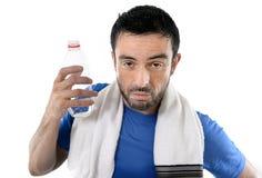 Homem do esporte atlético que mantém a garrafa de água que limpa suada para fora em seguida imagem de stock royalty free