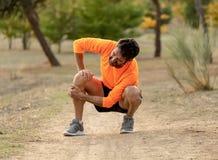 Homem do esporte ferido ao exercitar ou ao correr guardando seu joelho que grita na dor foto de stock royalty free