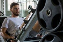 homem do esporte que faz exerc?cios com a m?quina da imprensa do p? no gym da aptid?o workout Treinamento fotografia de stock royalty free