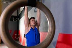 Homem do exercício dos anéis na suspensão do gym foto de stock royalty free