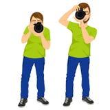 Homem do fotógrafo que toma fotos em duas poses diferentes Fotografia de Stock Royalty Free