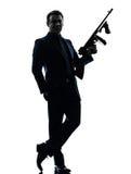 Homem do gângster que guarda a silhueta da metralhadora de thompson Imagens de Stock Royalty Free