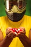 Homem do headshot do close up que veste a máscara facial amarela da camisa, a verde e a preta da proteção que sustenta a pilha do fotografia de stock royalty free