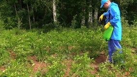 Homem do jardineiro em plantas de batata impermeáveis do pulverizador do workwear vídeos de arquivo