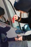 Homem do ladrão que guarda a chave de fenda que quebra no carro imagens de stock