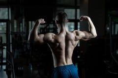 Homem do lerdo que está forte no Gym foto de stock