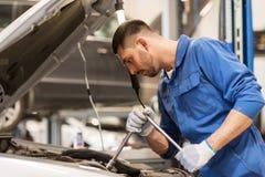 Homem do mecânico com a chave que repara o carro na oficina Fotos de Stock Royalty Free