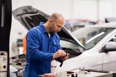 Homem do mecânico com a chave que repara o carro na oficina Foto de Stock