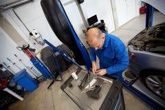 Homem do mecânico com a chave que repara o carro na oficina Fotos de Stock