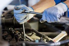 Homem do mecânico com a chave que repara o carro na oficina Imagem de Stock Royalty Free