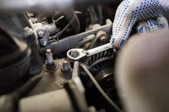 Homem do mecânico com a chave que repara o carro na oficina Foto de Stock Royalty Free