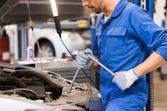 Homem do mecânico com a chave que repara o carro na oficina Imagem de Stock
