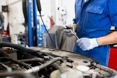 Homem do mecânico com a chave que repara o carro na oficina Fotografia de Stock