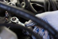 Homem do mecânico com a chave que repara o carro na oficina Fotografia de Stock Royalty Free