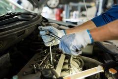 Homem do mecânico com a chave que repara o carro na oficina Imagens de Stock Royalty Free