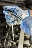 Homem do mecânico com a chave que repara o carro na oficina Imagens de Stock
