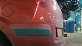 Homem do mecânico na garagem do automóvel que trabalha sob a parte inferior de um carro video estoque