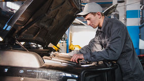 Homem do mecânico na garagem do automóvel que processa o diagnóstico do motor - verificando na capa do carro para ver se há SUV l Imagem de Stock Royalty Free