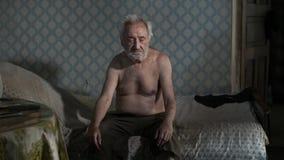 Homem do mendigo que senta-se em uma cama vídeos de arquivo
