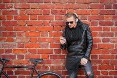 Homem do moderno com a bicicleta que está pela parede de tijolo e que escuta a música Imagens de Stock