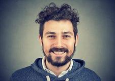 Homem do moderno no hoodie cinzento que sorri felizmente na câmera foto de stock royalty free