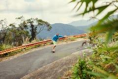 Homem do moderno que longboarding extremamente nos trópicos Fotos de Stock Royalty Free