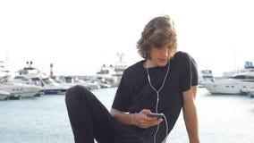 Homem do moderno que senta-se no longboard usando seu telefone vídeos de arquivo