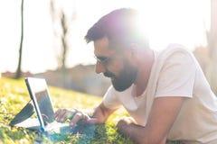 Homem do moderno que usa uma tabuleta digital em um parque fotografia de stock