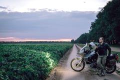 Homem do motociclista no casaco de cabedal que está exterior com sua motocicleta da aventura, usos um smartphone, fora do concei fotografia de stock royalty free