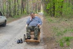 Homem do motorista que descansa fora de seu carro que dorme em uma balançar-cadeira de vime fotos de stock