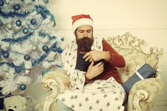 Homem do Natal com a barba cara séria no livro lido fotografia de stock