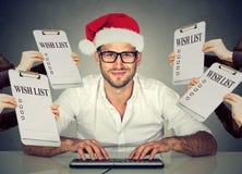 Homem do Natal no chapéu de Santa que recebe pedidos de presente que compra em linha Imagem de Stock Royalty Free