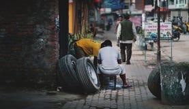 Homem do Nepali dois que repara o pneu de carro quebrado na oficina de reparações do carro Imagem de Stock