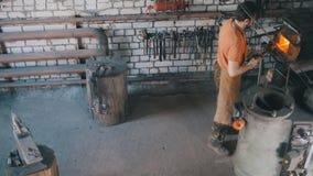 Homem do ofício - o ferreiro retira o detalhe do metal do fogo, vista superior foto de stock