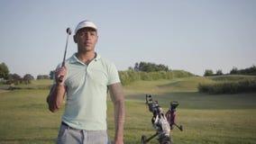 Homem do Oriente Médio bem sucedido seguro de sorriso bonito do retrato com um clube de golfe que está em um campo de golfe em bo vídeos de arquivo